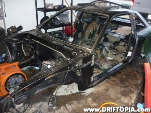 The bare s13 chassis sitting on the garage floor.