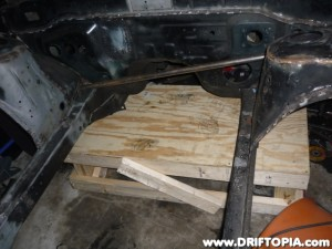 The bare 240sx chassis has been raised on two wooden platforms to prepare for the replacement of the crimped frame rails.